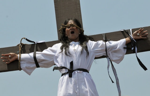 This is a girl on a cross with actual nails pierced through her skin as a re-enactment of the crucifixion.